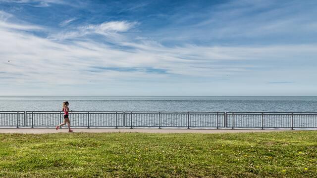 海が見える場所を走っている女性