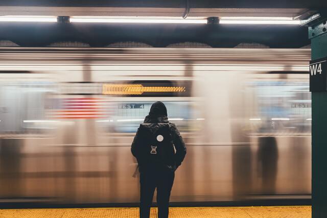 電車のホームにたたずむ女性